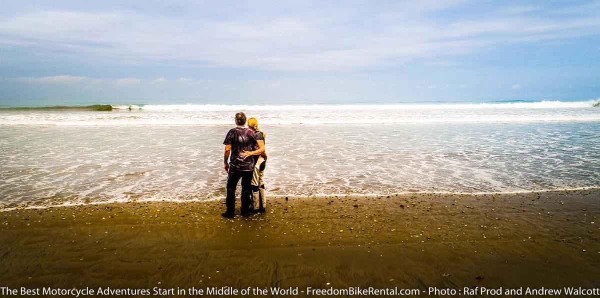 couple embracing on an ecuador beach during a motorcycle tour