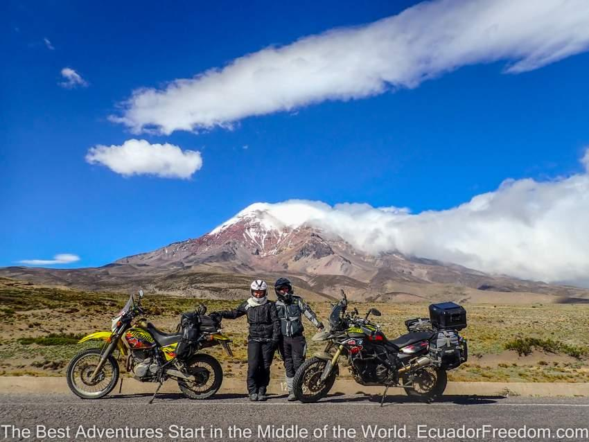 man and woman standing with two adventure motorcycles in front on chimborazo