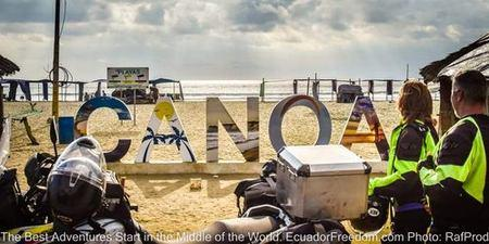 Canoa beach with two motorcyclists arriving at the Pacific Coast in Ecuador