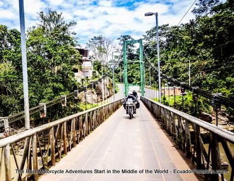 riding motorcycle across metal bridge in puerto misahualli ecuador
