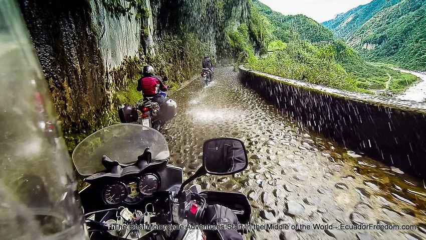 riding motorcycle to banos under waterfall
