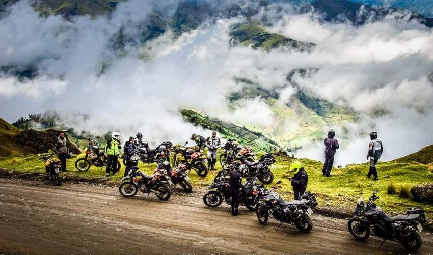 several adventure motorcycle riders in the andes mountains with clouds below