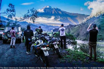 adventure motorcyclists and a jeep stop to view a mountain and the amazon basin in Ecuador