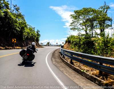 couple riding two up on a motorcycle on road going into the Ecuador Amazon basin