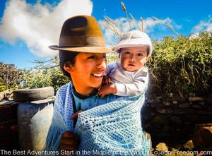 indigenous woman of the quilotoa loop in ecuador with baby smiling at motorcyclist