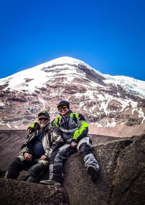 two adventure motorcyclists resting from an adventure motorcycle tour with chimborazo mountain in the background