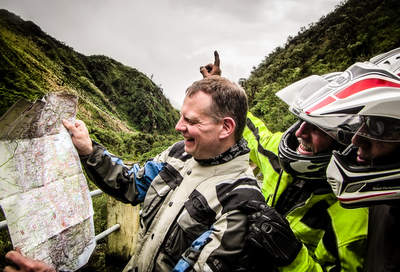 motorcyclists lost in ecuador looking at a map upside down