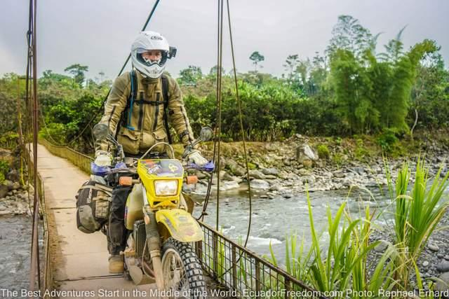 riding suzuki dr650 dual sport motorcycle over a metal bridge in ecuador