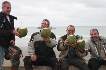 motorcyclists drinkng coconut on beach in ecuador