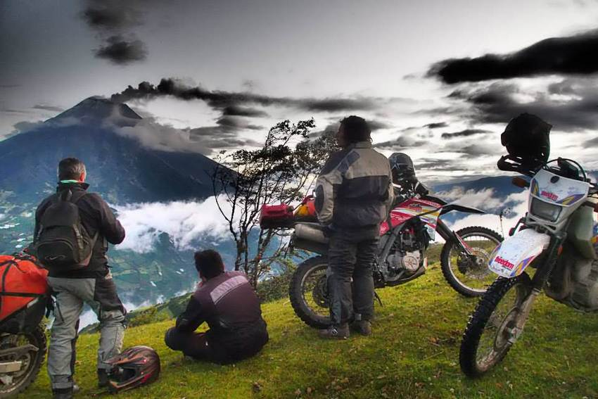 motorcycle tour group looking at erupting volcano in ecuador