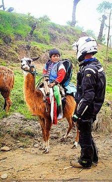 talkiung to a boy on a llama ecuador motorcycle adventure toru